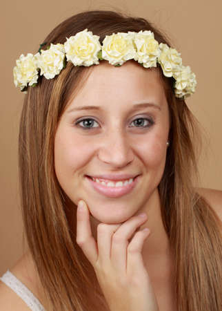 fake smile: young caucasian woman with crown of fake flowers