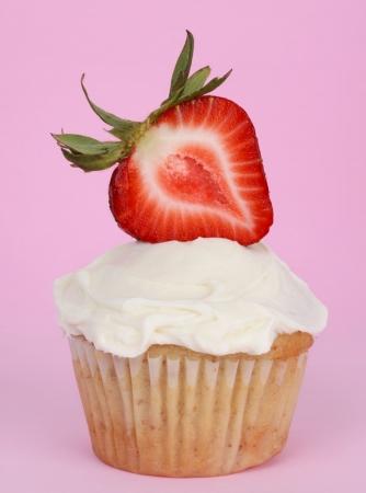 イチゴのスライスと白いアイシング カップケーキ 写真素材