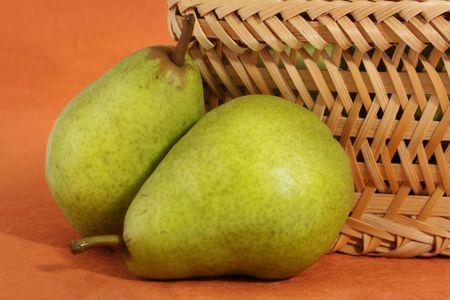 two bartlett pears near a wicker basket photo