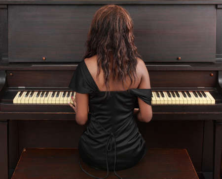 portrait of beautiful black woman sitting at piano 스톡 콘텐츠