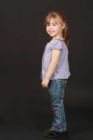 cute caucasian little blond girl, black background photo
