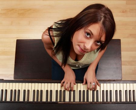 beautiful brunette caucasian girl sitting at piano photo