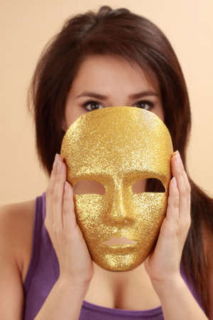 beautiful hispanic young woman holding a gold mask Stock fotó