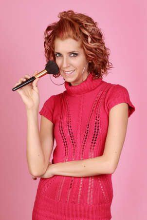 cute woman holding a makeup brush, pink background Stock Photo - 6261203