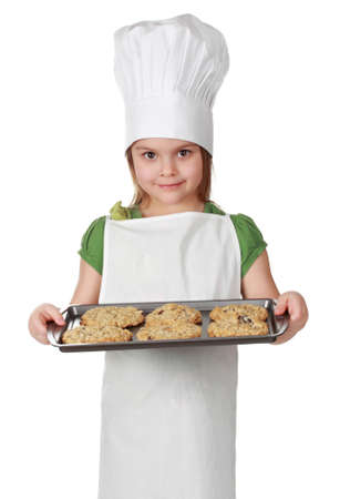 white sheet: little girl with chief hat holding a cookie sheet, isolated on white