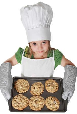 ni�os cocinando: ni�a con sombrero jefe sosteniendo una hoja de cookie, aislada en blanco