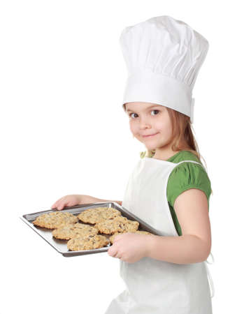 little girl with chief hat holding a cookie sheet, isolated on white