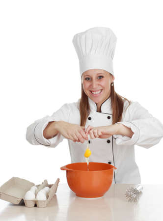 breaking: woman wearing chef cook uniform, breaking eggs Stock Photo