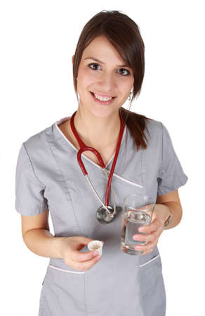 Nurse wearing grey uniform, holding medication and water Stockfoto