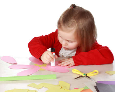 Cute little girl making a flower with paper and glue Standard-Bild
