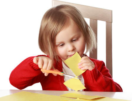 Cute little girl cutting off piece of yellow paper