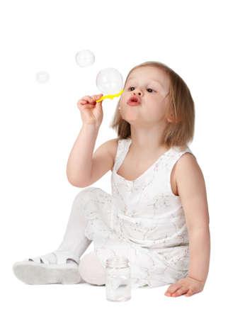 cute little blond girl blowing bubble soap photo