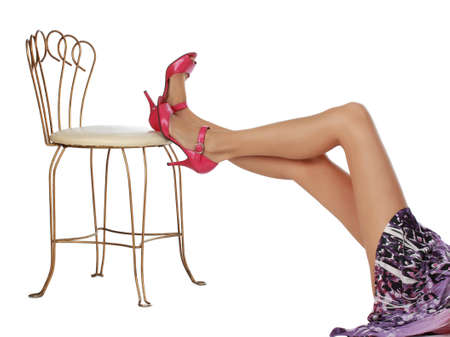 girl legs on a white fancy chair, white background photo