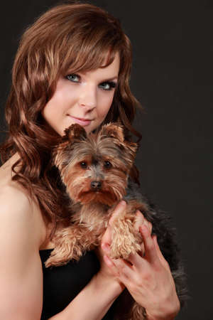 portrait of a beautiful young woman holding a tiny yorkshire terrier dog Banque d'images