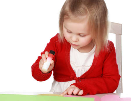 Cute little girl making a flower with paper and glue photo