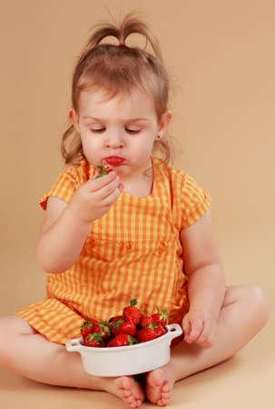 cute little girl eating fresh strawberries, beige background photo