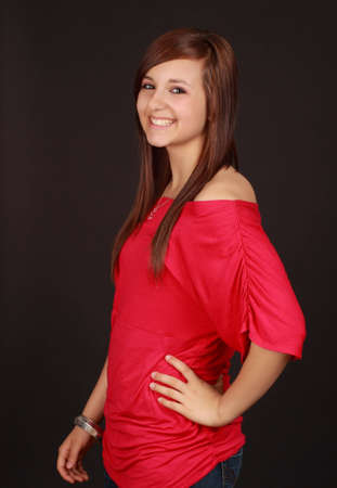 portrait of a cute teen girl, red shirt, black background