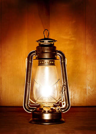 old oil lamp light over wood plank background Stock Photo