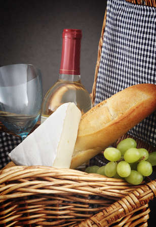 picnic basket with wine, bread and cheese.