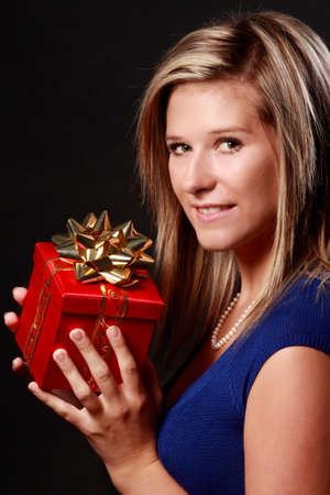 portrait of a beautiful young caucasian blond woman holding a wrapped gift isolated on black background Stock Photo - 7907095
