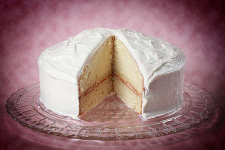 round: nice white vanilla cake with a missing piece on a glass plate Stock Photo