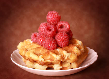 belgian waffles with fresh raspberries in a pink plate, brown background 版權商用圖片
