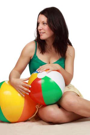 beach ball girl: lindo joven mujer sosteniendo una pelota de playa colorida, aislada en blanco