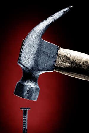 釘とハンマー、赤の背景にクローズ アップ