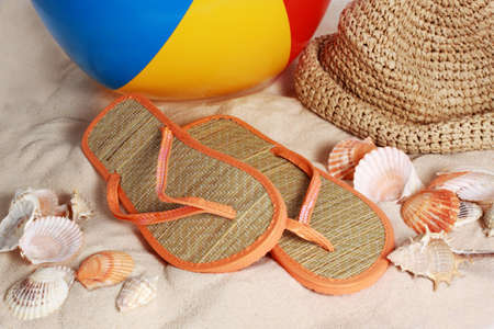 inflatable colorful beach ball, flip flops and hat on sand and seashell photo