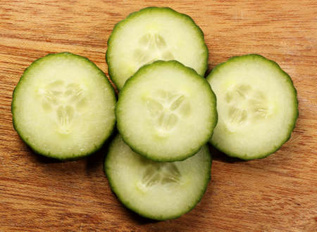 english cucumber: sliced english cucumber on wood plank, top view