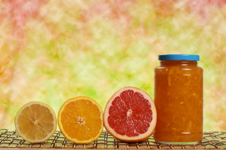 jar of citrus marmalade with some fresh fruits