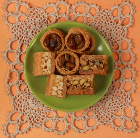 baklava patries in a green plate over knitted tablecloth Imagens