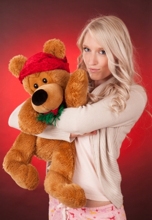 Beautiful young woman holding a Christmas teddy bear