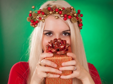 cute girl holding a xmas gift, green background