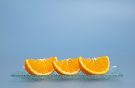 Three pieces of fresh oranges on a plate, blue background Imagens