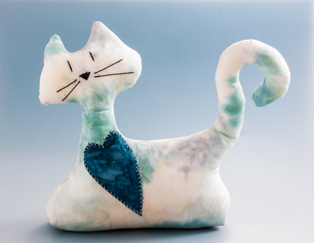 White and blue homemade cat plush door holder with heart in its neck, blue background