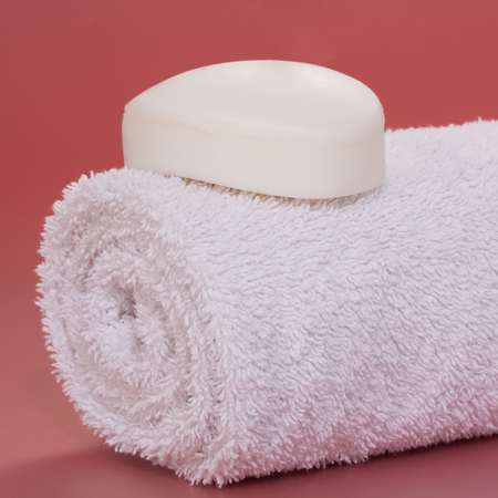 White soap bar placed over a rolled clean bath towel