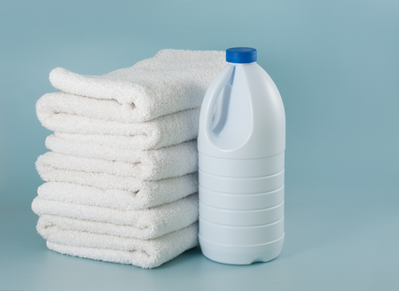 Laundry white bleach bottle place beside stack of bath towel Imagens