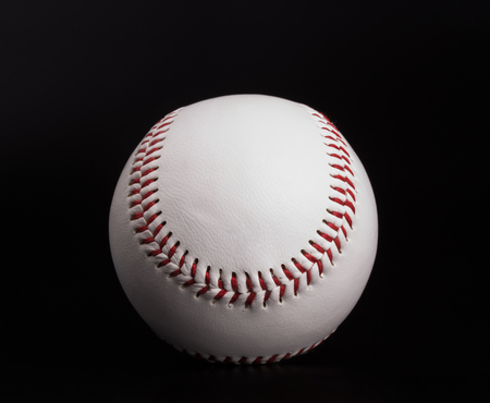 One new white baseball ball with red thread isolated on black background Imagens