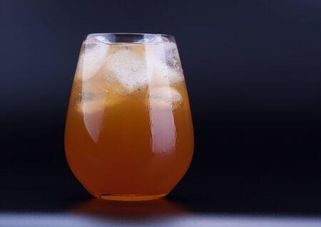 Big glass of ice tea with ice cubes, black background Reklamní fotografie