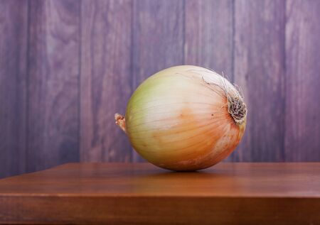 Closeup on a whole fresh onion as food ingredient on a wooden table Reklamní fotografie