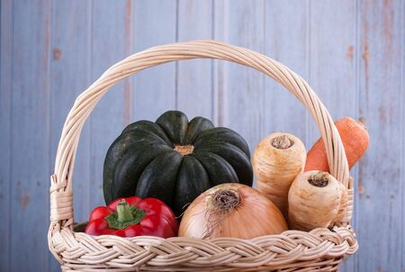 Colorful raw fresh whole vegetables in a wicker basket