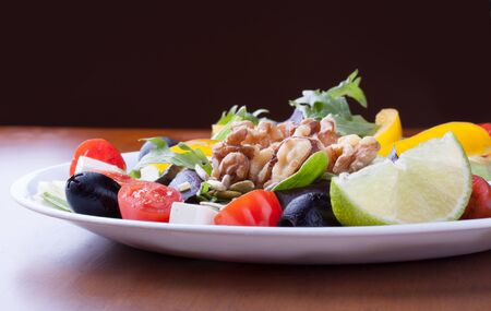 Closeup on a fresh healthy green salad with olive, cheese and walnuts in a white plate Reklamní fotografie