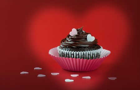 Chocolate cupcake with nice chocolate icing garnish with pink eatable hearts on red background