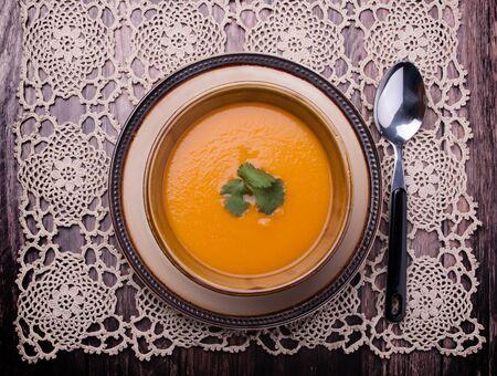 Closeup to vieuw on a carrot cream-soup with cilantro