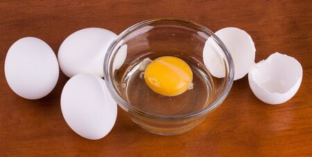 Broken egg in a glass bowl with whole eggs and shell on wood table Reklamní fotografie