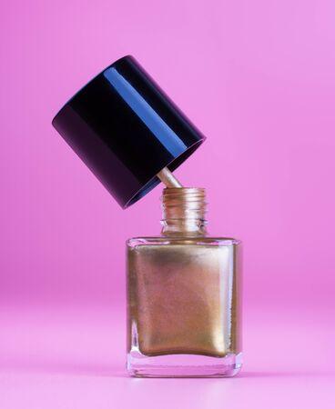 Nice bottle of gold nail polish, pink background Reklamní fotografie