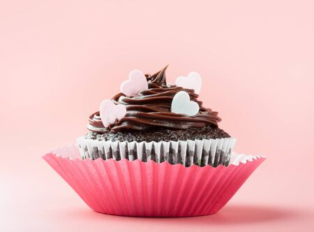 chocolate cupcake with chocolate icing and eatable hearts, in nice decorative paper mold, pink background Reklamní fotografie