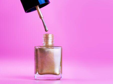 Opened bottle of gold nail polish, pink background Reklamní fotografie