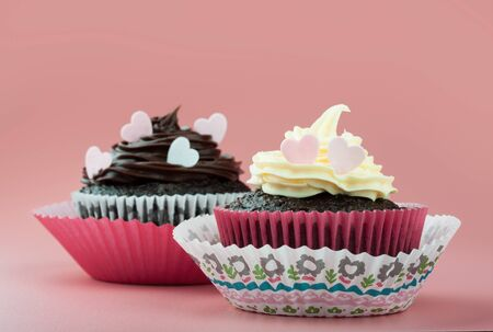 chocolate cupcake with vanilla chocolate icing and eatable hearts, in nice decorative paper mold, pink background